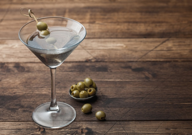 Cocktail de gin vodka martini dans le verre d'origine avec des olives dans un bol en métal et des bâtons de bambou sur une surface en bois. espace pour le texte
