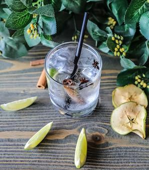 Cocktail avec glace à la lime cannelle anis pomme sèche vue latérale