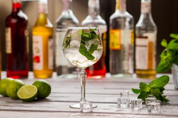 Cocktail avec glace en verre. feuilles de menthe et citrons verts. sirop sucré pour boisson hugo. la boisson est presque prête.