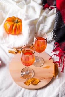 Cocktail halloween, boisson orange à la citrouille avec des épices sur la planche de bois au lit blanc