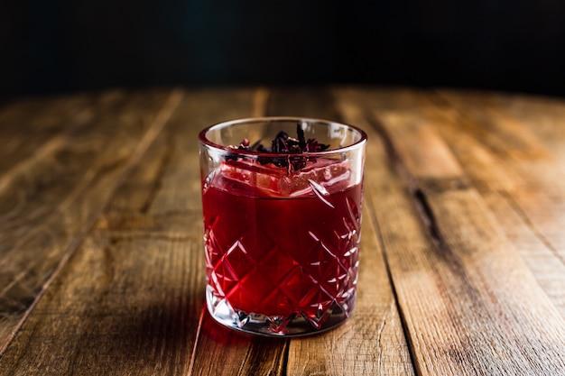Un cocktail d'hibiscus avec un glaçon dans un verre de roches sur une table en bois