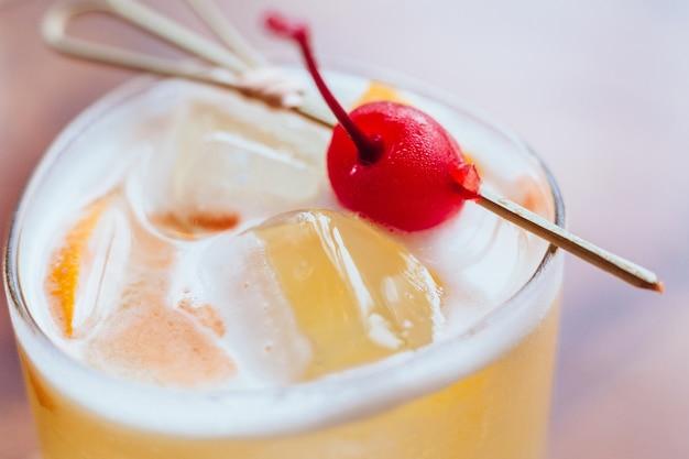 Cocktail jaune rempli de tranches de citron et de glace servies avec des cerises fraîches