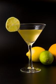 Cocktail jaune avec une tranche de citron et au fond un citron