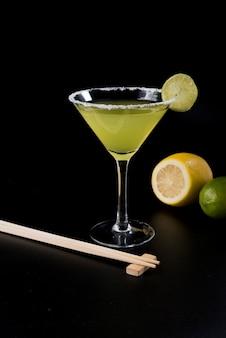 Cocktail jaune avec tranche de citron, baguettes, citron vert et citron sur fond noir