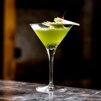 Cocktail de kiwis dans un verre à martini garni de tranches de pomme sur une brochette de bambou