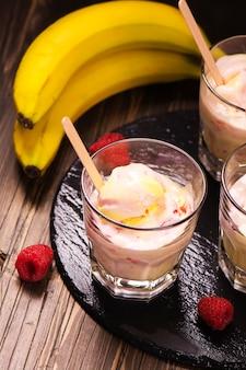 Cocktail de lait rafraîchissant avec des boules de crème glacée, de framboises et de banane