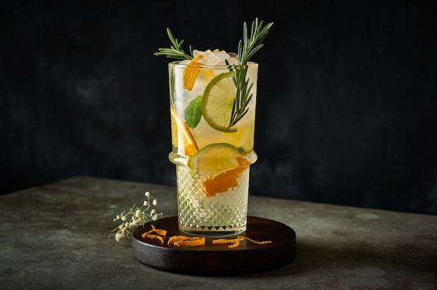 Cocktail de limonade d'été rafraîchissante maison avec jus d'orange glace pilée romarin et agrumes