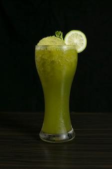 Cocktail de limonade vert menthe éclatant garni de citron et menthe sur fond noir