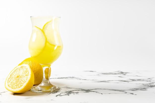 Cocktail limoncello au citron dans un beau verre sur fond clair et table en marbre