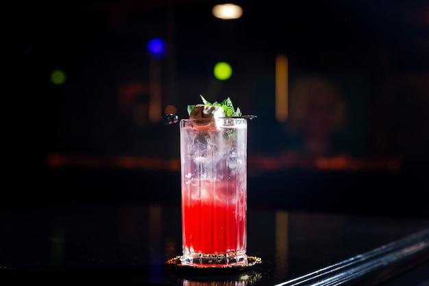 Un cocktail long drink rouge et transparent en couches dans un verre highball collins, avec de la glace, garni de menthe et de guimauve