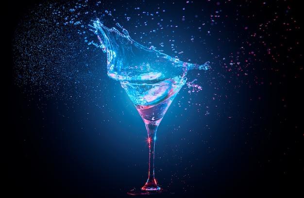 Cocktail lumineux avec du citron dans un verre et des éclaboussures d'eau