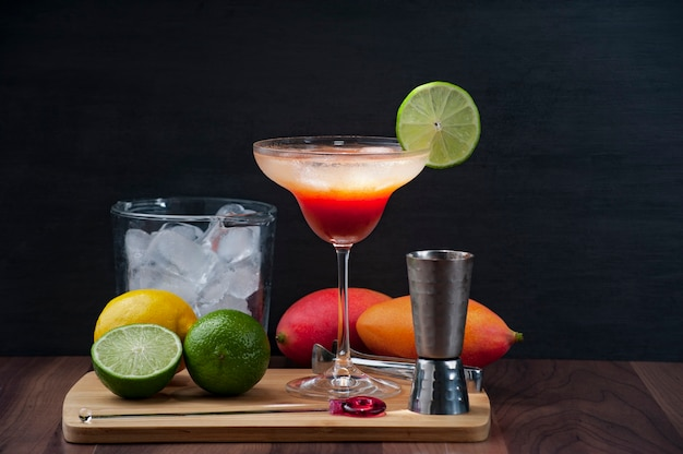 Cocktail de mangue, vodka, citron et glace sur une planche de bois accompagné d'un seau à glace