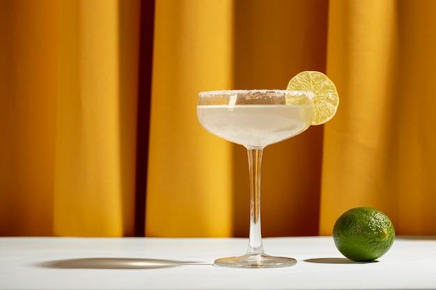 Un cocktail margarita au citron avec des quartiers de citron vert et du sel sur une table blanche contre un rideau jaune
