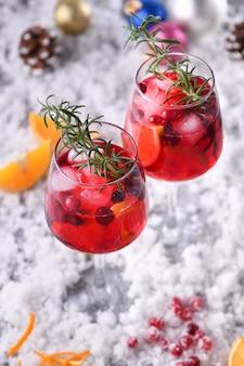 Cocktail margarita aux canneberges, orange et romarin. un cocktail parfait pour une fête de noël