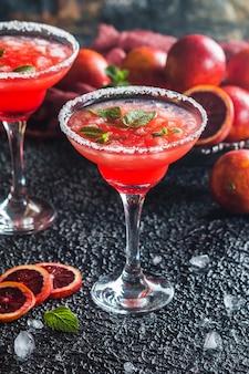 Cocktail margarita à l'orange sanguine à la menthe et à l'orange rouge dans un verre à cocktail bordé de sel