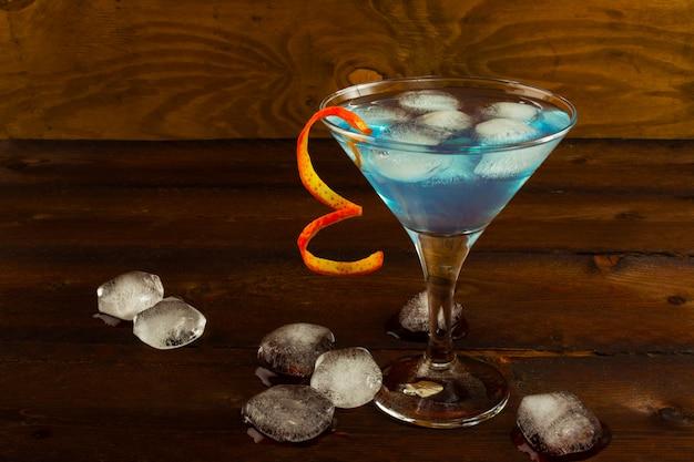 Cocktail martini bleu sur la surface en bois sombre