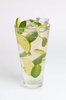 Cocktail à la menthe, citron vert et glace pilée sur fond blanc