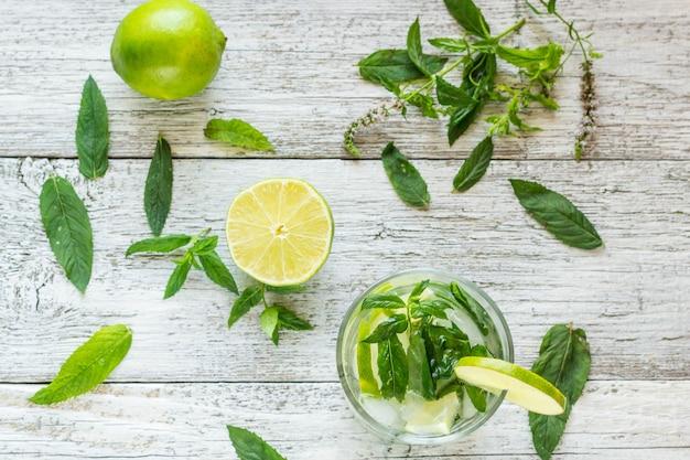Cocktail mojito au citron vert et menthe dans un verre à whisky sur une table en bois blanc vue de dessus