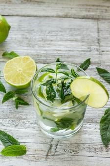 Cocktail mojito au citron vert et menthe dans un verre à whisky sur une table en bois blanc