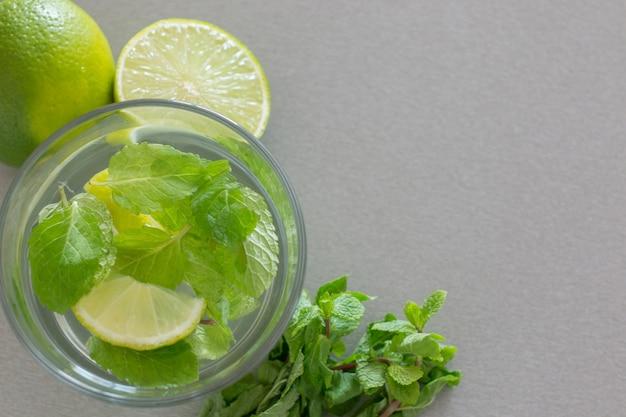 Cocktail mojito au citron vert et menthe en verre sur un mur gris