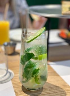 Cocktail mojito au citron vert et menthe en verre sur table en bois