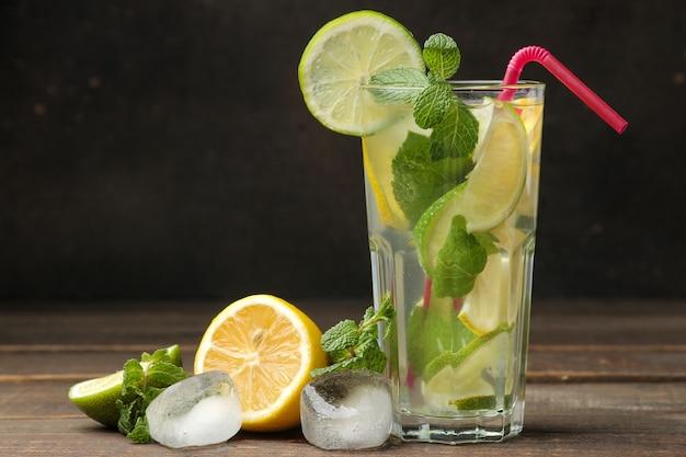 Cocktail mojito dans un verre au citron vert, menthe et citron sur une table marron en bois