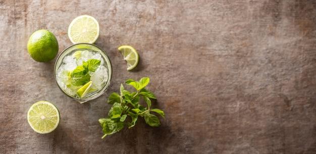 Cocktail mojito avec du rhum blanc, des herbes à la menthe, du citron vert et du soda sur le comptoir du bar - vue de dessus.