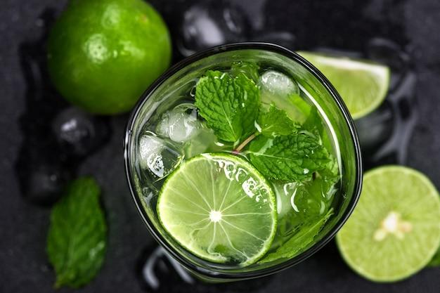 Cocktail mojito frais avec du citron vert frais et feuille de menthe sur fond de pierre noire