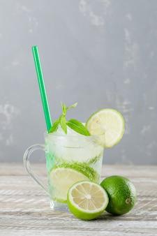Cocktail mojito glacé dans une tasse de limes, paille, menthe vue latérale sur fond de bois et de plâtre