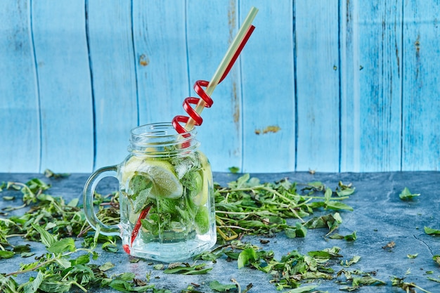 Cocktail mojito avec des tranches de citron vert et de menthe sur table bleue avec des feuilles de menthe fraîche