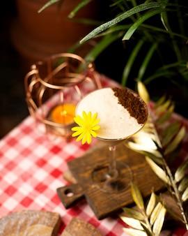 Cocktail avec mousse et poudre de cacao décoré de fleurs