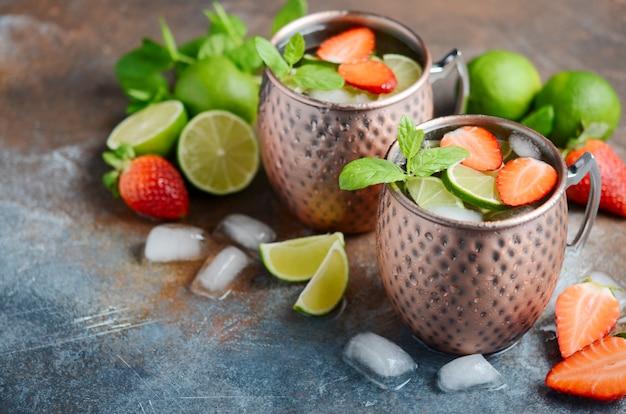 Cocktail mulet à la bière de gingembre, à la vodka, au citron vert, aux fraises et à la menthe dans des tasses en cuivre