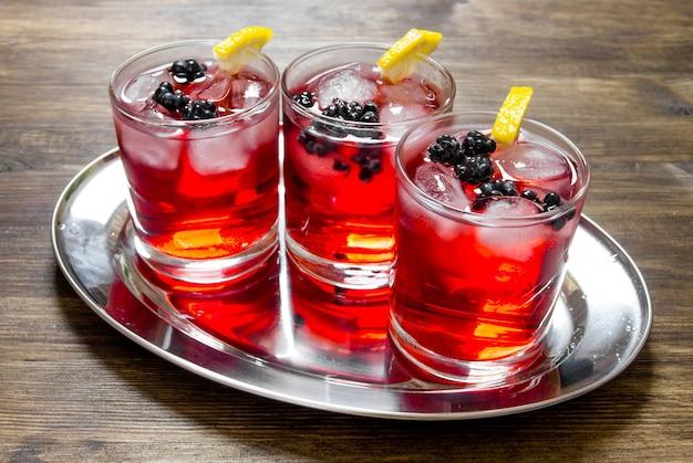Cocktail de mûres. cocktails de baies en verre avec glace et citron sur table en bois.