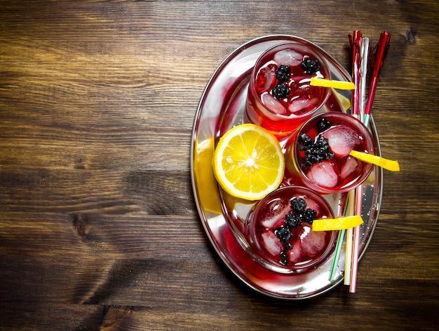 Cocktail de mûres. cocktails de baies en verre avec de la glace et du citron sur la table en bois.vue de dessus
