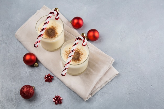 Cocktail de noël au lait de poule à la cannelle, servi dans deux verres dans des décorations de noël.