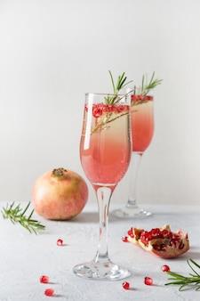 Cocktail de noël à la grenade au romarin, vin mousseux sur tableau blanc. boisson de noël.