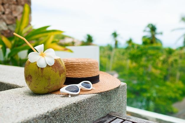 Cocktail de noix de coco décoré de plumeria, chapeau de paille et lunettes de soleil sur la table.