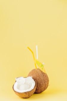 Cocktail de noix de coco fraîche avec une paille sur fond jaune, copiez l'espace.