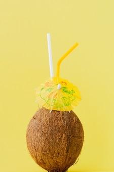 Cocktail de noix de coco fraîche avec une paille sur jaune