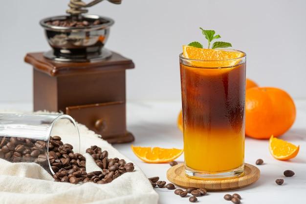 Cocktail d'orange et de café sur la surface blanche.