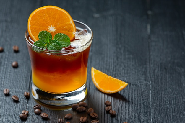 Cocktail d'orange et de café sur la surface sombre.