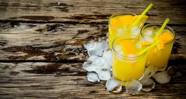 Cocktail d'orange fraîche trois cocktails d'oranges fraîches avec de la glace et de la paille sur fond de bois
