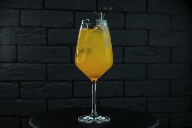 Cocktail orange-jaune alcoolisé sucré de fruits avec des glaçons avec du jus d'orange et du rhum blanc sur une table dans un bar sur un fond noir
