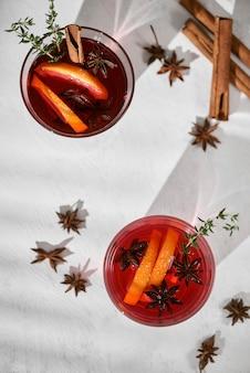 Cocktail orange avec rhum, liqueur, tranches de poire et thym sur table blanche, mise au point sélective