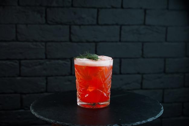 Cocktail orange-rouge doux avec martini avec vodka et tonic et menthe est debout sur la table sur un café de table en bois noir. dégustation d'alcool. cocktail d'auteur dans un verre vintage en cristal