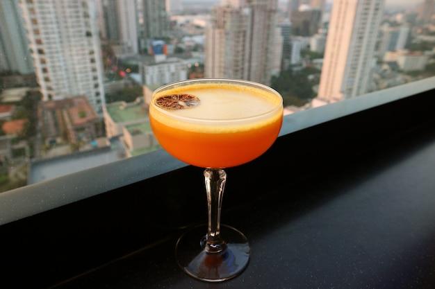 Cocktail orange vif sur le bar sur le toit avec vue urbaine aérienne