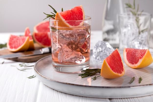 Cocktail de pamplemousse au romarin sur table en bois blanc