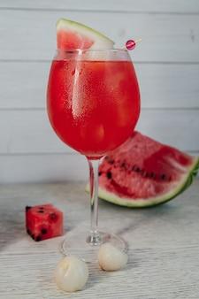Cocktail de pastèque dans un grand verre à vin sur une table en bois
