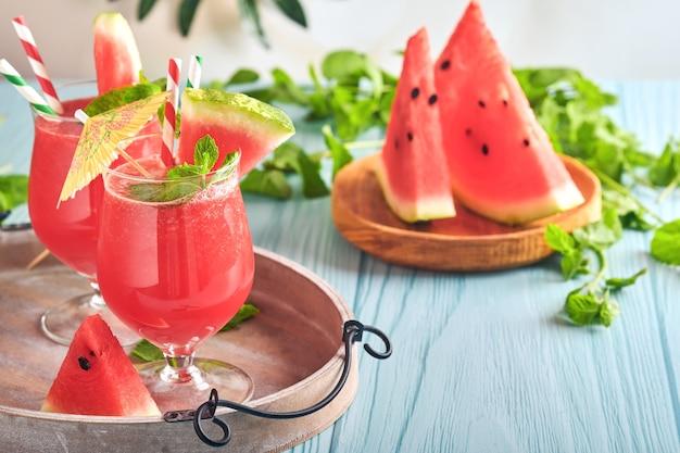 Cocktail de pastèque à la menthe et à la glace. boissons rafraîchissantes d'été dans des verres sur une table en bois bleue. concept d'une alimentation saine en été.
