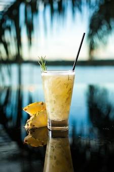 Cocktail pinacolada au romarin et ananas sur fond tropical